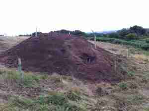 Artificial Sett complete. Large mound of earth in a field showing one of the entrances.